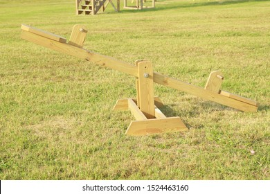 Wooden Seesaw in a Field of Green Grass in the Fall