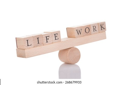 Wooden seesaw representing imbalance between Life and Work isolated over white background
