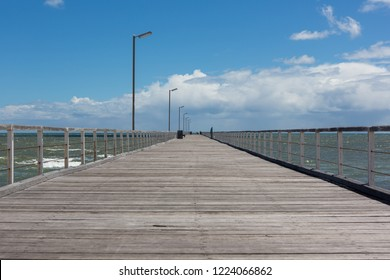 The wooden Semaphore jetty with a blue sky and white clouds above taken at Semaphore beach South Australia on 7th November 2018