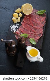 Wooden serving board with carpaccio made of raw marbled beef and seasonings, vertical shot on a black stone surface