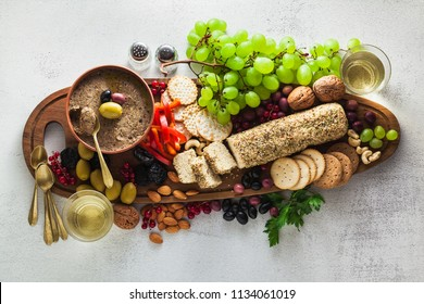 Wooden serving board with vegan snacks. Pate of olives and cheese from cashew nuts with herbs. Healthy appetizer with grapes, nuts, and dried fruits on a black slate table. and white wine in a glass.