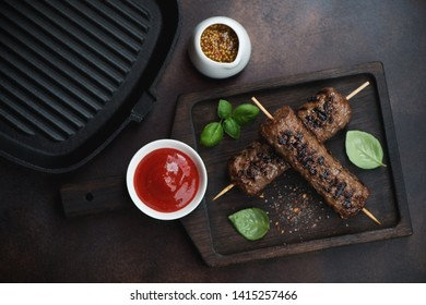 Wooden serving tray with bbq marbled beef kabobs on wooden skewers, view from above on a brown metal background
