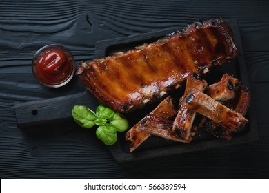 Wooden serving tray with bbq pork ribs over black wooden surface, top view