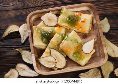 Wooden serving tray with flapjacks and fruit sauce topping on a rustic wooden background, studio shot