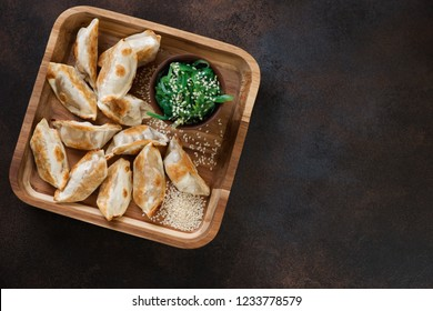 Wooden serving tray with fried gyoza dumplings, flatlay over dark brown metal background, horizontal shot with copyspace