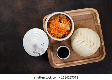 Wooden serving tray with korean steamed traditional tin-pun, salad and dipping sauce. Flatlay on a brown metal background