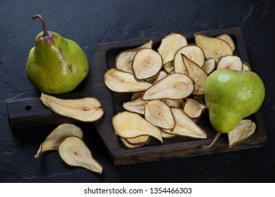 Wooden serving tray with pear fruit chips over black stone background