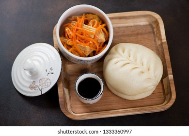 Wooden serving tray with steamed korean pjan-se, soy sauce and salad, studio shot on a dark brown metal background