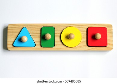 A wooden shape sorter puzzle with a triangle, circle, square and rectangle