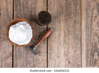 Wooden shaving razor with shaving brush and shaving foam on a rustic wooden table - vintage shaving accessories - top view