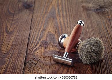 Wooden shaving razor and brush on wooden background