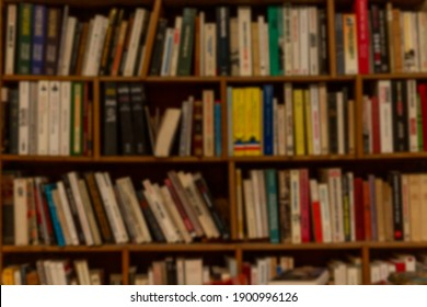 Wooden shelf with books in a row. Education and knowledge. Blurred.