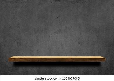 Wooden shelf over dark concrete wall background