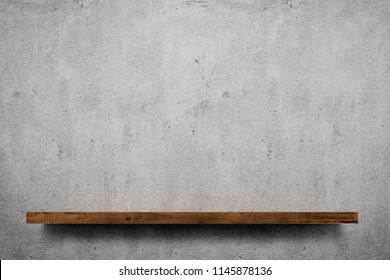 Wooden shelf over grey concrete wall background