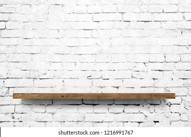 Wooden shelf over white brick wall background