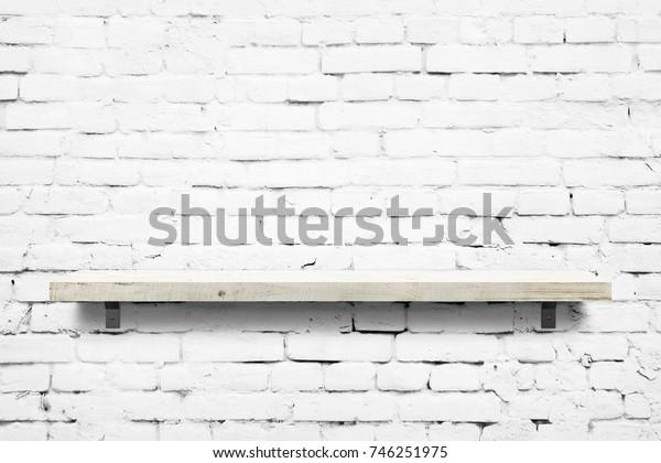 Wooden shelf over white brick wall background