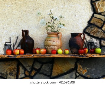 Wooden shelf with pottery and apples