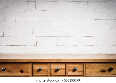 wooden shelf and wall of white bricks