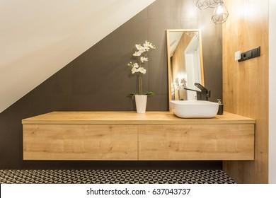 Wooden shelf with washbasin and mirror in cozy bathroom