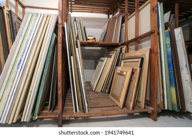 Wooden shelves at art gallery storage full of pictures and art equipment