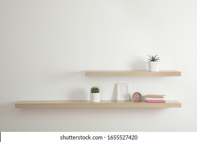 Wooden shelves with books and decorative elements on light wall