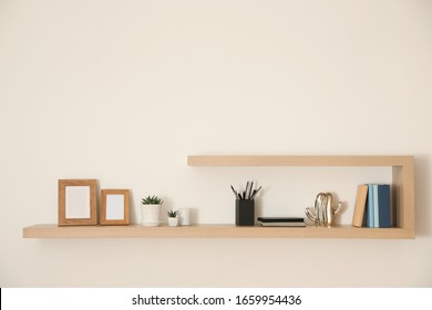 Wooden shelves with books, photo frames and decorative elements on light wall - Shutterstock ID 1659954436