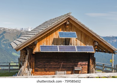 Wooden shepherd lodge with solar panels and Alpine mountain landscape in Western Carinthia, Austria.