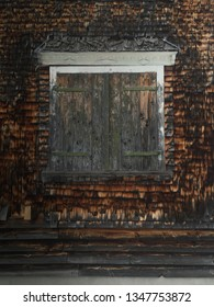 Wooden shingle facade with closed wooden shutters