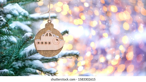 wooden ship toy on Christmas tree, natural winter background. Christmas and New Year holiday concept. boat, symbol of sea cruise, travel. beautiful festive winter season