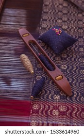 Wooden Shuttle and Spool on cotton thread in Loom. Old shuttle loom made by wooden. Weaving shuttle on the cotton fabric. Weaving Tool And Fabric On Weaving Machine