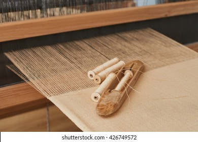 Wooden Shuttle and Spool on Sackcloth thread in Loom