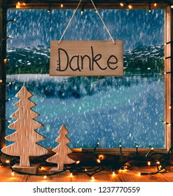 Wooden Sign With German Calligraphy Danke Means Thank You. Window Or Frame With Fairy Lights And Chrismtas Tree. View To Beautiful Winter Scenery