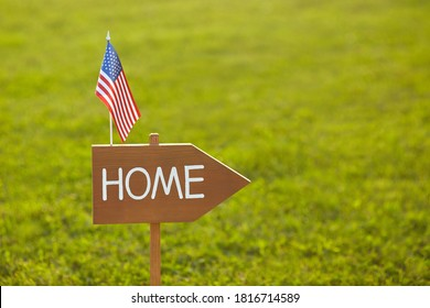 Wooden sign with the inscription Home and American flagAmerican Independence Day. The concept of patriotism. Real estate concept. Home sweet home.