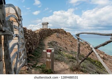 A wooden sign on the Cami de Cavalls coastal walk in Minorca island.
