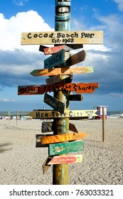 wooden sign on Cocoa beach, florida, USA, pointing to different places in USA with the distance to the places on each sign, the wooden sinage is attached to a wooden post and are vertically lined up