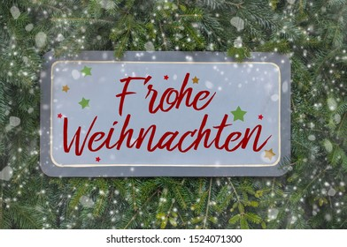Wooden sign on fir branches with the german word for merry christmas - Frohe Weihnachten