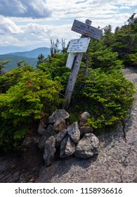 A wooden sign on a mountain peak in Maine, marking a junction with the Appalachian Trail.