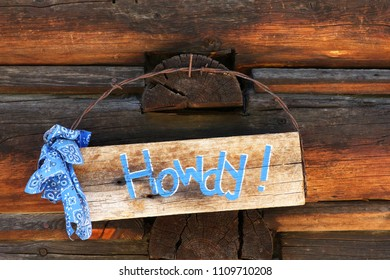 Wooden sign on side of log cabin that says Howdy!