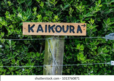 A wooden sign on a walking track indicates how to reach the township of Kaikoura, New Zealand
