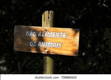 """Wooden Sign in Portuguese language. It say """"don´t feed the animals"""". Black background. Sunlight"""
