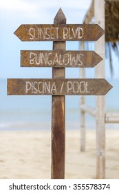 Wooden sign post standing on the beach and providing the direction to the Bungalows and the swimming pool on the beach in Punta Sal, Peru