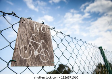 A wooden sign prohibiting the use of bicycles on a metal fence and a blue sky with white clouds in the background.