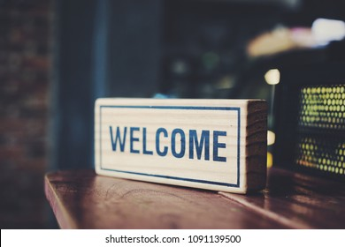 """A wooden sign reads """"Welcome"""" on a wooden table in a coffee shop.Vintage color style"""