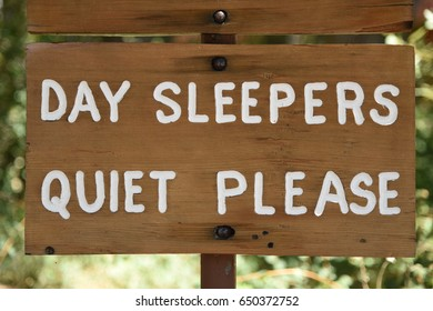 "Wooden sign saying ""Day Sleepers Quiet Please"""