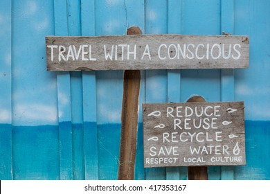 Wooden sign saying to travel with a conscious wooden on blue  wall background.