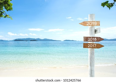 wooden sign with text 2019,2018 and 2017, Over Blurred blue sea and sand beach with cloudy blue sky , Image for New year 2019 Concept.