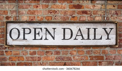 Wooden sign with text open daily on a vintage brick wall