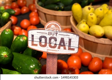 wooden sign with word signage reading buy local produce with tomatoes yellow squash and zucchini background