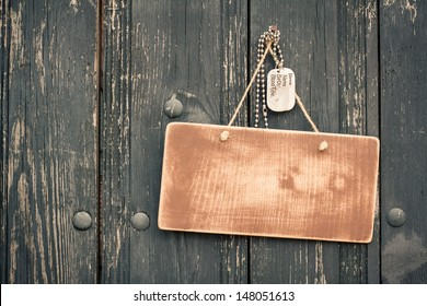 Wooden signboard with army dog tags hanging on wood planks background