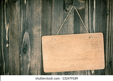 Wooden signboard frame with rope hanging on planks background